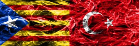 卡塔龙尼亚对土耳其拷贝肩并肩被安置的烟旗子 加泰罗尼亚语和土耳其的浓厚色的柔滑的烟旗子复制 免版税图库摄影