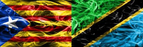 卡塔龙尼亚对坦桑尼亚拷贝肩并肩被安置的烟旗子 加泰罗尼亚语和坦桑尼亚的浓厚色的柔滑的烟旗子复制 免版税库存图片