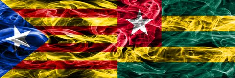 卡塔龙尼亚对多哥拷贝肩并肩被安置的烟旗子 加泰罗尼亚语和多哥的浓厚色的柔滑的烟旗子复制 图库摄影