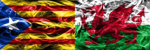 卡塔龙尼亚对威尔士拷贝肩并肩被安置的烟旗子 加泰罗尼亚语和威尔士的浓厚色的柔滑的烟旗子复制 库存照片