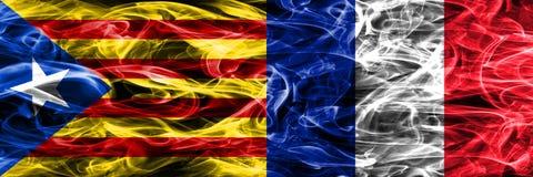 卡塔龙尼亚对法国拷贝肩并肩被安置的烟旗子 加泰罗尼亚语和法国的浓厚色的柔滑的烟旗子复制 免版税库存图片