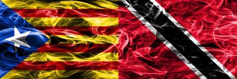卡塔龙尼亚对特立尼达和多巴哥拷贝肩并肩被安置的烟旗子 加泰罗尼亚语和特立尼达的浓厚色的柔滑的烟旗子和 免版税图库摄影