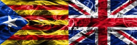 卡塔龙尼亚对英国拷贝肩并肩被安置的烟旗子 加泰罗尼亚语和英国co的浓厚色的柔滑的烟旗子 免版税库存照片