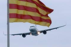 卡塔龙尼亚的空客320 Vueling和旗子 库存图片