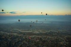 卡帕多细亚,土耳其:清早顶视图从气球、有薄雾的风景与雾与山和五颜六色的气球 免版税库存照片
