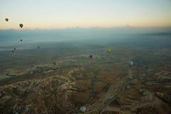 卡帕多细亚,土耳其:清早顶视图从气球、有薄雾的风景与雾与山和五颜六色的气球 免版税库存图片