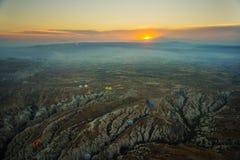 卡帕多细亚,土耳其:清早顶视图从气球,与雾的有薄雾的风景与山 库存图片