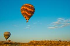 卡帕多细亚,格雷梅,安纳托利亚,土耳其:日落登陆在山卡帕多细亚格雷梅国立公园的热空气气球 免版税库存图片
