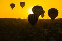 卡帕多细亚,格雷梅,安纳托利亚,土耳其:气球的剪影反对黄色天空的 在的美好的黎明 库存图片
