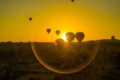 卡帕多细亚,格雷梅,安纳托利亚,土耳其:气球的剪影反对黄色天空的 在的美好的黎明 库存照片