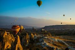 卡帕多细亚,格雷梅,安纳托利亚,土耳其:气球飞行风景充满活力的看法在卡帕多细亚谷的在日出光芒 库存照片