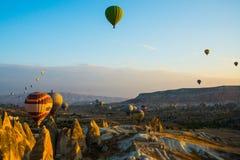卡帕多细亚,格雷梅,安纳托利亚,土耳其:气球飞行风景充满活力的看法在卡帕多细亚谷的在日出光芒 免版税库存照片