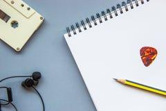 卡式磁带、耳机、铅笔、吉他采撷和空白的笔记本 免版税库存照片