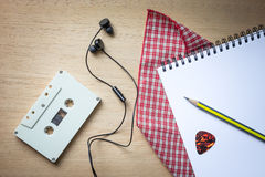 卡式磁带、耳机和空白的笔记本在木头歌曲作者的 免版税库存图片