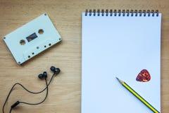 卡式磁带、耳机和空白的笔记本在木头歌曲作者的 免版税库存照片