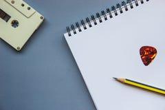 卡式磁带、铅笔、吉他采撷和空白的笔记本在灰色地板上 库存照片