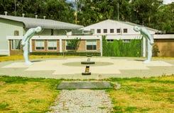 卡扬贝火山,厄瓜多尔- 2017年9月05日:赤道线纪念碑,两向人雕象标记扔石头的点 免版税库存图片