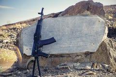 卡拉什尼科夫在花岗岩平板、小山和蓝天背景的攻击步枪特写镜头在背景中 免版税库存照片