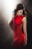 卡拉OK演唱党 美丽的唱歌的女孩 红色的妇女与话筒 免版税库存照片