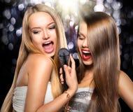 卡拉OK演唱 有话筒的秀丽女孩 图库摄影