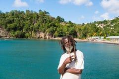 卡斯特里, stLucia - 2015年11月26日:非洲人展示胜利或和平姿态在蓝色海 有胡子和dre的老无家可归的人 免版税库存图片