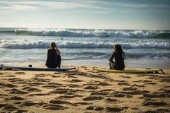 卡普布雷通,法国- 2017年10月4日:后面观点的妇女女孩冲浪者坐在冲浪板的沙滩 免版税库存照片