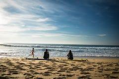 卡普布雷通,法国- 2017年10月4日:后面观点的妇女女孩冲浪者坐在冲浪板的沙滩 免版税库存图片