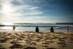 卡普布雷通,法国- 2017年10月4日:后面观点的妇女女孩冲浪者坐在冲浪板的沙滩 库存图片