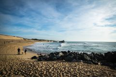 卡普布雷通,法国- 2017年10月4日:走在沙滩和冲浪者的人们捉住在大西洋海岸的波浪在风景蓝天 库存图片