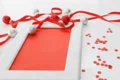 贺卡模板由白色框架和红牌制成与红色丝带,银和红色球和红色五彩纸屑 库存图片