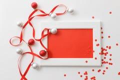 贺卡模板由白色框架和红牌制成与红色丝带,银和红色球和红色五彩纸屑 免版税库存照片