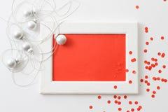 贺卡模板由白色框架和红牌制成与银色闪亮金属片、球和红色五彩纸屑 免版税库存照片