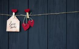 卡片以欲望爱华伦泰` s心脏自然绳子,并且垂悬在土气纹理背景的红色别针,复制空间 免版税库存图片