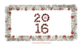 贺卡由与红色圣诞节球, 2016的银色闪亮金属片框架制成做了玉米和中国象形文字猴子的 免版税图库摄影