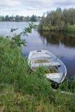 卡累利阿人的湖在早上、草、树和一条偏僻的小船2 库存图片
