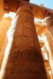 卡纳克神庙寺庙复合体在卢克索 与法老王和他的妻子的雕刻的polychromed专栏 免版税库存图片