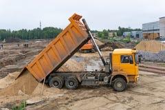 卡车卸载在建造场所的沙子 库存图片