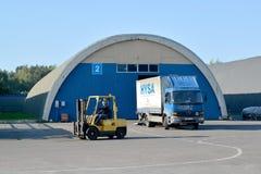 卡车和自动装卸机在一个现代仓库的疆土 免版税库存照片