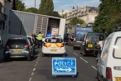 卡车在与司机的陡峭的小山黏附了和警察和标志 免版税库存照片
