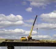 卡车在大厦天桥的起重机工作 免版税库存图片