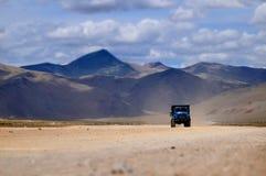 卡车通过落寞沙漠高山 免版税库存图片