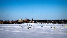卡车驾驶在有冬天鱼议院的冻湖上在背景中在一个晴朗的早晨 库存图片