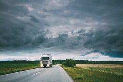 卡车,拖拉机单位,原动力,在行动的牵引单位在乡下公路,高速公路在欧洲 在上的多云天空 免版税库存图片