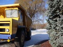 卡车 工业采矿设备 反对美丽的绿色冷杉和天空蔚蓝背景  库存照片