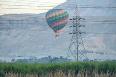 12/11/2018卢克索,埃及上升在一片绿色绿洲的日出的热空气气球在沙漠 库存照片