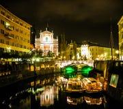 卢布尔雅那在晚上: 桥梁,教会,小船 免版税库存图片