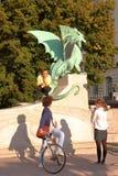 卢布尔雅那,斯洛文尼亚- 2012年9月15日:学生谈论在龙前面在龙桥梁 免版税库存照片