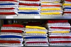 卧具在架子的壁橱 毛巾在卷折叠了 在垂悬夫人的和人的衣物的挂衣架 库存图片