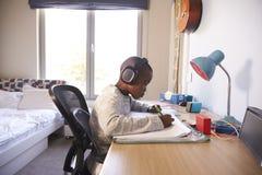 卧室佩带的耳机和做家庭作业的年轻男孩 库存照片
