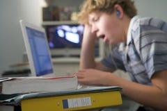 卧室使用打呵欠的年轻人的男孩膝上型计算机 库存照片